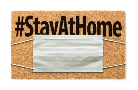 Welcome Mat With Medical Face Mask and #Stay At Home Text Isolated on White Amidst The Coronavirus Pandemic.