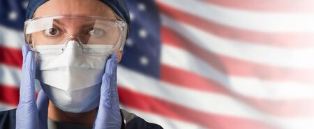 Doctor or Nurse Wearing Medical Personal Protective Equipment (PPE) Against The American Flag Banner.