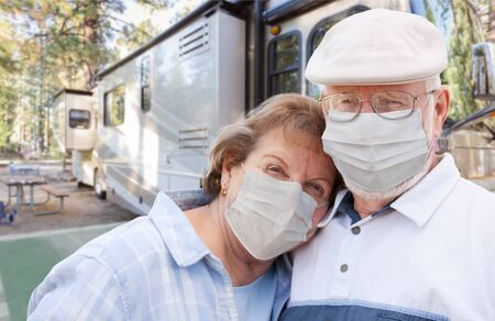 Senior Couple Wearing Medical Face Masks In Front of Their Beautiful RV At The Campground.
