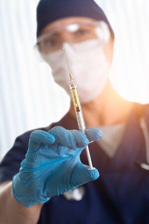 Doctor or Nurse Holding Medical Syringe with Needle.