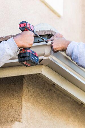 Workers Attaching Aluminum Rain Gutter to Fascia of House. Фото со стока