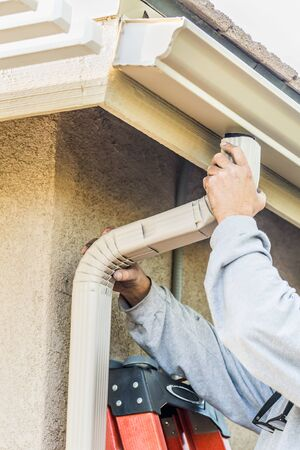 Worker Attaching Aluminum Rain Gutter and Down Spout to Fascia of House. Фото со стока