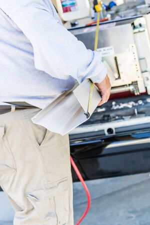 Worker Measuring Rain Gutter Processing Through Seamless Shaping Machine. Фото со стока