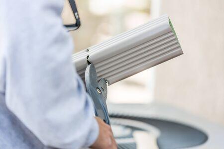 Worker Cutting Aluminum Rain Gutter With Heavy Shears. Фото со стока