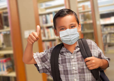 Hispanic Boy Wearing Face mask with Books, Apple, Pencil and Paper at Library. Фото со стока