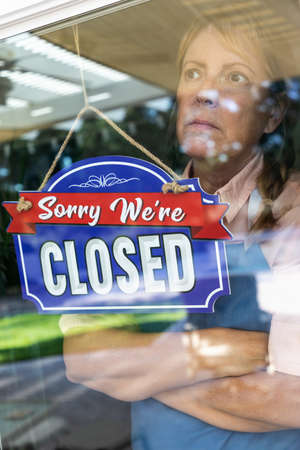 Female Store Owner Wearing Medical Face Mask Turning Sign to Closed in Window.