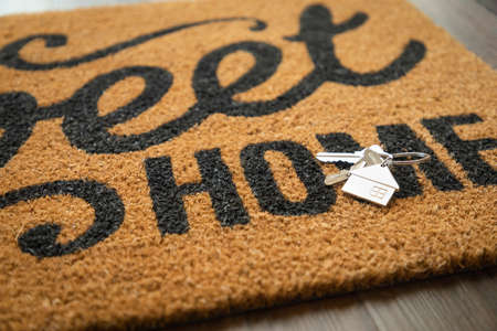 New House Keys and Keychain Rests on Home Sweet Home Welcome Mat.