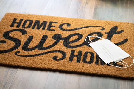 Medical Face Masks Rests on Home Sweet Home Welcome Mat Amidst The Coronavirus Pandemic.