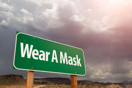 Wear A Mask Green Road Sign Against Ominous Stormy Cloudy Sky.