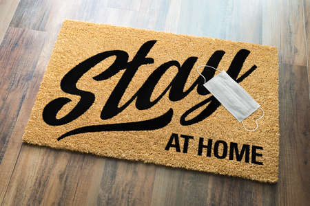 Stay At Home Welcome Mat with Medical Face Face Resting On Floor. Фото со стока