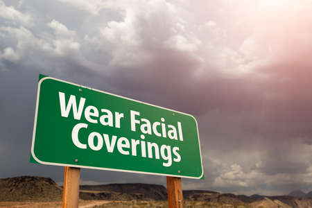 Wear Facial Coverings Green Road Sign Against Ominous Stormy Cloudy Sky. Фото со стока