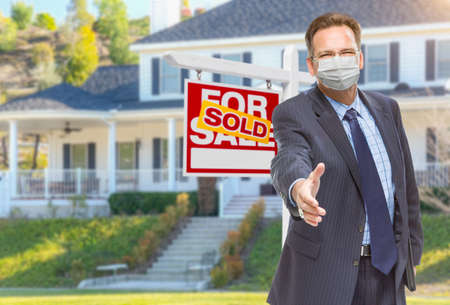 Male Real Estate Agent Reaching for Hand Shake Wearing Medical Face Mask with Sold For Sale Sign Behind.