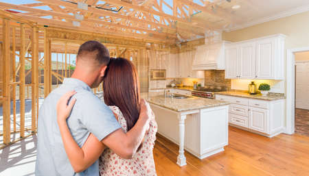 Young Military Couple Facing House Construction Framing Gradating Into Finished Kitchen Build. Banque d'images