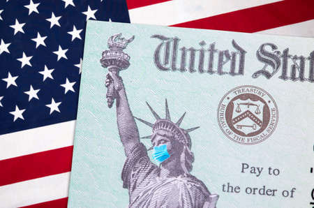 United States IRS Stimulus Check with Statue of Liberty Wearing Medical Face Mask Resting on American Flag.