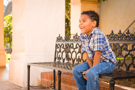 Handsome African American and Mexican Boy Sitting on Park Bench.
