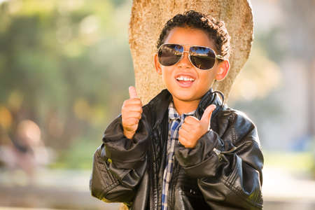 African American and Mexican Boy Dressed Up with Sunglasses and Leather Jacket. Archivio Fotografico