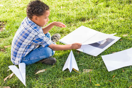 African American and Mexican Boy Learning How to Fold Paper Airplanes Outdoors on the Grass. Archivio Fotografico