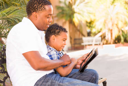 African American Father and Mixed Race Son Using Computer Tablet on Bench in Park.