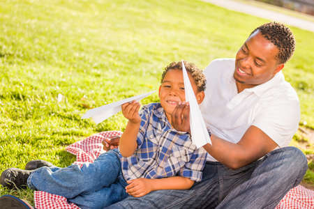Happy African American Father and Mixed Race Son Playing with Paper Airplanes in the Park. Archivio Fotografico