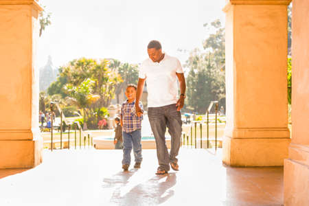 Happy African American Father and Mixed Race Son Walking At The Park. Archivio Fotografico