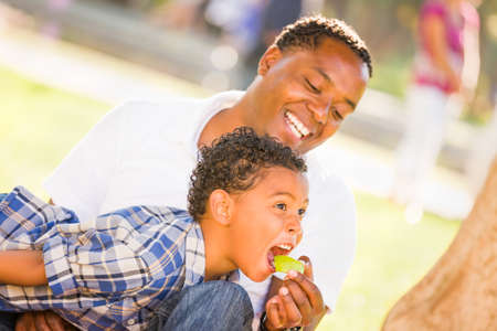 African American Father and Mixed Race Son Eating an Apple in the Park.