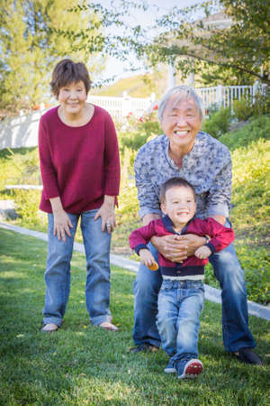 Happy Chinese Grandparents Having Fun with Their Mixed Race Grandson Outside. Standard-Bild