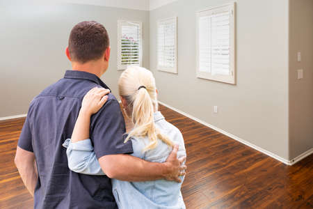 Young Couple Facing Empty Room of New House.