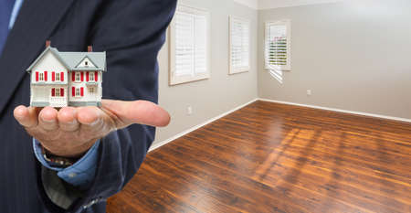 Real Estate Agent Holding Model Home Iside Empty Room of New House.