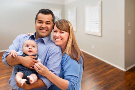 Young Couple With Baby In Empty Room of New House. Archivio Fotografico