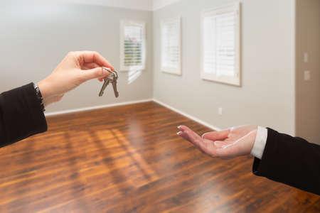 Real Estate Agent Hands Over New House Keys Inside Empty Room.