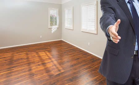 Real Estate Agent Reaches for Handshake Inside Empty Room of New House.