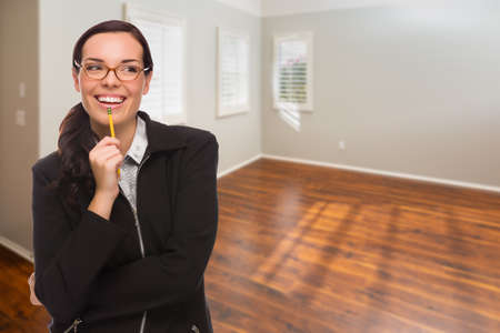Woman With Pencil In Empty Room of New House. Archivio Fotografico