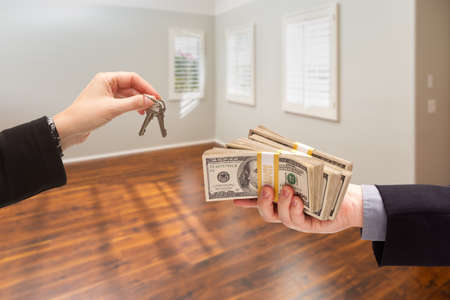 Real Estate Agent Hands Over New House Keys For Cash Inside Empty Room. Archivio Fotografico