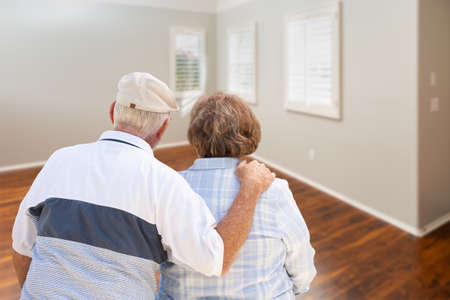 Senior Couple Facing Empty Room of New House. Archivio Fotografico