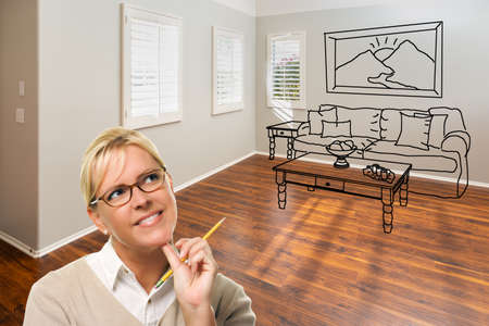 Woman With Pencil In Empty Room of New House with Couch and Table Drawing on Wall.