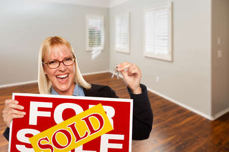 Woman with Sold For Sale Real Estate Sign and Keys In Empty Room of New House. Archivio Fotografico