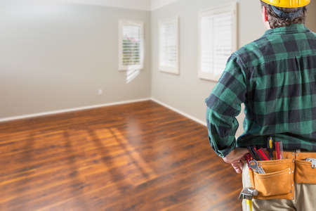 Contractor Wearing Toolbelt and Hard Hat Facing Empty Room with Hard Wood Floors.