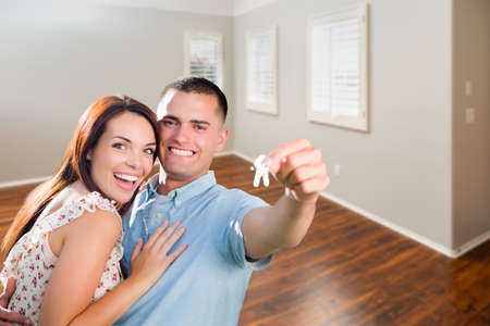 Young Military Couple Showing Off House Keys in Empty Room of New Home.