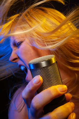 Female vocalist under gelled lighting sings with passion into condenser microphone.