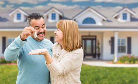 Mixed Race Couple in Front of House with Keys. Foto de archivo