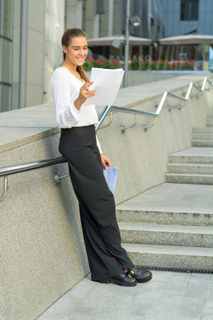 long pants: business woman shirt light portfolio long hair young woman business woman pants smile happy girl street stairs lifting climbing stairs a white shirt a nice girl a slender girl white teeth beautiful teeth bizenss center steps railings summer spring fall da