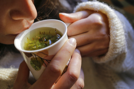to get warm: A young woman on the couch and with sage tea on the hand.