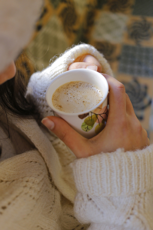 to get warm: The young woman on the couch and with cappuccino on the hand.