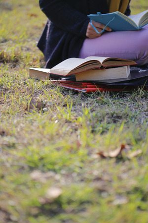late teens: There is student reading book on the University campus area.