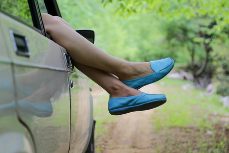 Young woman enjoying to the travel in the nice forest with her boyfriends classic car. With blues shoes. Stock Photo