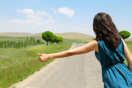 The Hitchhiking woman hand on the beautiful road side.