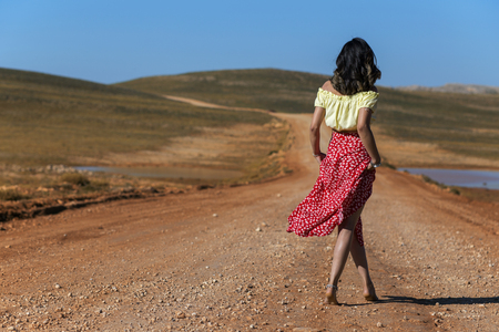 The gypsy woman without shoes on the ground. It is a flower stuck in hair.