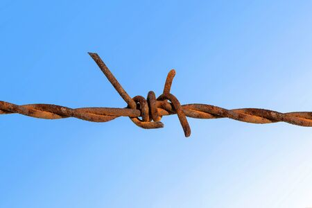 Rusty barbed wire with blue sky.