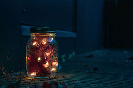 Glass mason jar with LED fairy lights and dried red maple leaves on wooden patio in the dark in fall autumn