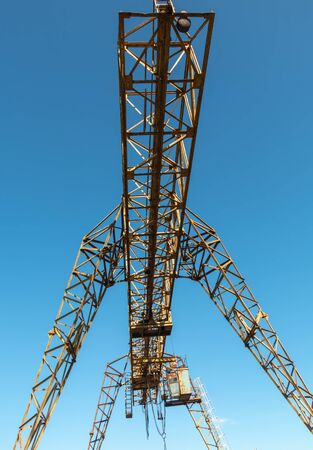 Vintage working gantry crane rusty yellow, bottom view, close-up against a blue spring sky